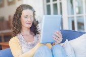 Brunette relaxing on the couch with tablet — ストック写真