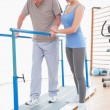 Senior man walking with parallel bars and coach help  — Stock Photo #68971223