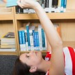 Student reading book lying on library floor — Stock Photo #68971717