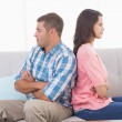 Angry couple with arms crossed sitting on sofa — Stock Photo #68971917