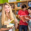 Female college student holding books in library — Stock Photo #68972175