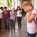 Sad schoolgirl with friends in background at school corridor — Stock Photo #68972785