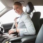 Businesswoman putting on her seat belt — Stock Photo #68974155