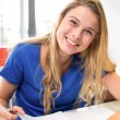 Female student writing notes in classroom — Stock Photo #68974549