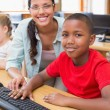 Cute pupil in computer class with teacher  — Stock Photo #68974595