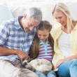 Parents and daughter playing with rabbit — Stock Photo #68975215