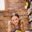 Cute little girl reading book in library — Stock Photo #68976251