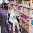 Smiling disabled student in library picking book — Stock Photo #68976355