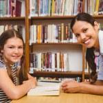 Female teacher and little girl in library — Stock Photo #68976579