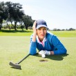 Female golfer looking at her ball on putting green — Stock Photo #68976899