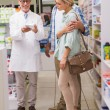 Pharmacist and customers talking about medication — Stock Photo #68977343