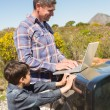Father and son in countryside using laptop — Stock Photo #68977379