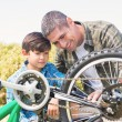 Father and son repairing bike — Stock Photo #68979551