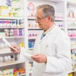 Senior pharmacist looking at medicine and prescription — Stock Photo #68979905