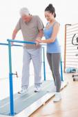 Senior man walking with parallel bars and coach help  — Stock Photo