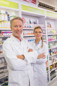 Smiling pharmacist and his trainee — Stock Photo