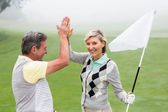 Golfing couple high fiving — Stock Photo