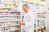 Pharmacist taking medicine from shelf — Stock Photo