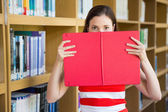 Student holding book over face — Stock Photo