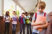 Sad schoolboy with friends in background at school corridor — Stock Photo