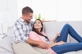 Couple looking at each other while relaxing on sofa — Stock Photo