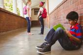 Schoolboy with friends in background at school corridor — Stock Photo