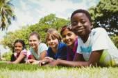 Retrato de crianças felizes, deitada na grama — Fotografia Stock