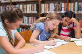 Cute pupils drawing in library — Stock Photo