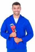 Smiling male mechanic holding monkey wrench — Stock Photo