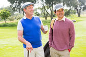 Golfing friends smiling and holding clubs — Stock Photo