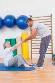 Trainer working with senior woman on exercise mat — Stock Photo