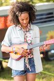 Pretty hipster playing the ukulele — Stock Photo