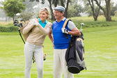 Golfing couple walking on the putting green — Stock Photo