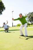 Golfing friends cheering on the putting green — Stock Photo