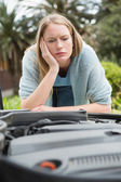 Thoughtful woman looking at engine  — Stock Photo