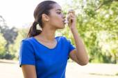 Pretty woman using her inhaler — Stock Photo