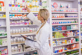 Junior pharmacist taking medicine from shelf — Stock Photo