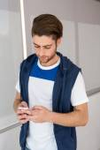 Handsome young man text messaging — Stock Photo