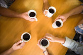 Hands holding coffee mugs on table — Photo