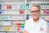 Senior pharmacist smiling at camera — 图库照片