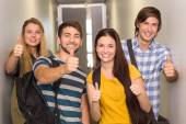 Happy students gesturing thumbs up at college corridor — Stock Photo