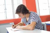 Male student writing notes in classroom — Stock Photo