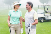 Golfing couple facing each other — Stock Photo