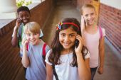 School kids using cellphones in school corridor — Stock Photo