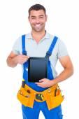 Repairman in overalls holding digital tablet — Stock Photo