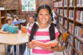 Cute pupil looking for books in library — Stock Photo