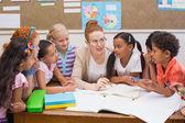 Professor e alunos trabalham juntos na mesa — Fotografia Stock