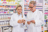 Pharmacist and trainee talking together about medication — Stock Photo