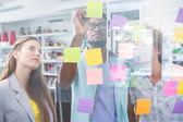 Creative team writing on adhesive notes — Стоковое фото