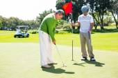 Golfer holding hole flag for friend putting ball — Stockfoto